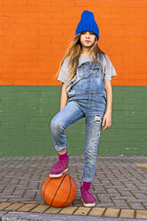 Young girl with foot on basketball - ERRF01245