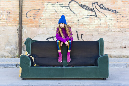 Girl wearing colorful clothing and sitting on a couch outdoors - ERRF01260