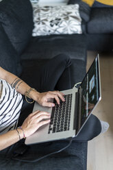 Man sitting on couch at home using laptop, partial view - AFVF02934