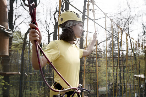 Young woman wearing yellow t-shirt and helmet in a rope course - EYAF00196