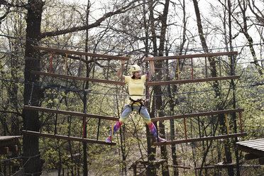 Young woman wearing yellow t-shirt and helmet in a rope course - EYAF00199