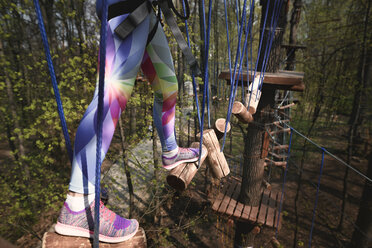 Young woman wearing yellow t-shirt and helmet in a rope course - EYAF00202