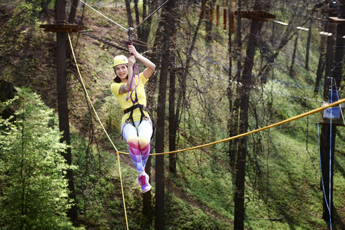 Young woman wearing yellow t-shirt and helmet in a rope course - EYAF00208
