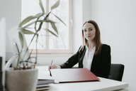 Portrait of confident young woman working at desk in office - AHSF00337