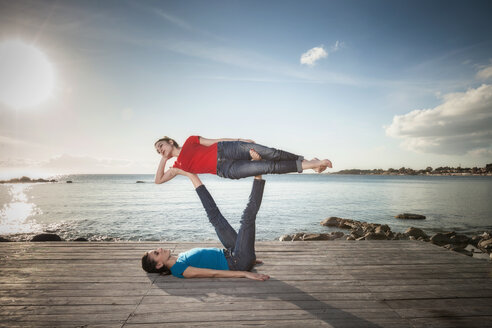Women practising acro yoga at seaside - CUF50663