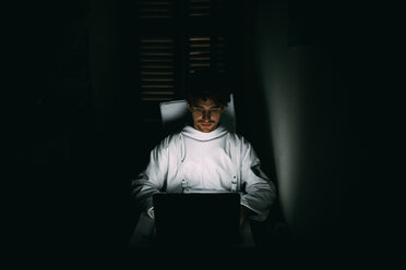 Astronaut using laptop in dark room - CUF50699
