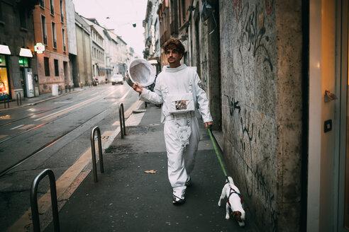 Astronaut walking pet dog on pavement - CUF50705