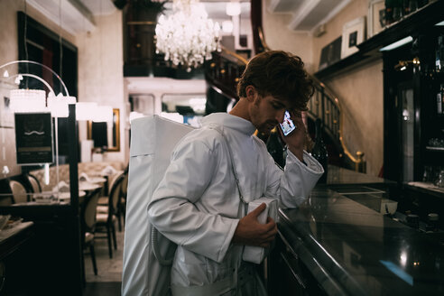 Astronaut using smartphone in restaurant - CUF50708