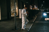 Astronaut using smartphone on pavement - CUF50714