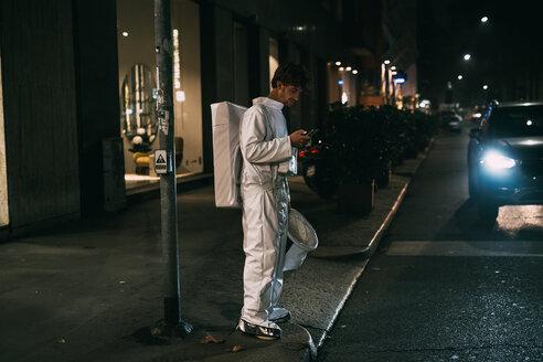 Astronaut using smartphone on pavement - CUF50714