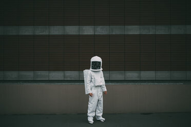 Astronaut standing against striped concrete wall - CUF50717