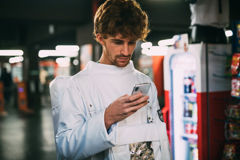 Astronaut using smartphone on train platform - CUF50720