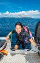 Female scuba diver boarding dinghy after a dive, portrait, Raja Ampat, Sorong, Nusa Tenggara Barat, Indonesia - CUF50825