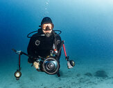 Underwater view of male diver with under water camera, portrait, Raja Ampat, Sorong, Nusa Tenggara Barat, Indonesia - CUF50870
