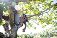 Man relaxing on tree, Pagudpud, Ilocos Norte, Philippines - CUF51023