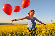 Girl with red balloons on rapeseed field, Eastbourne, East Sussex, United Kingdom - CUF51038