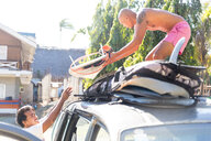 Man helping friend load surfboards on top of vehicle, Pagudpud, Ilocos Norte, Philippines - CUF51050