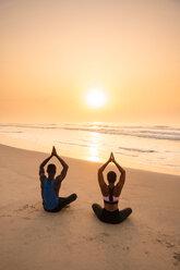 Couple practising yoga on beach - CUF51062