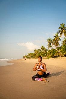 Woman practising yoga on beach - CUF51071