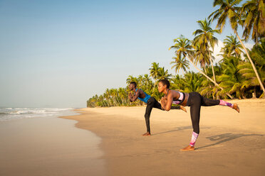 Couple practising yoga on beach - CUF51074