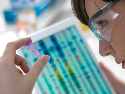 Female scientist examining DNA sample in eppendorf tube with results on digital tablet in laboratory - CUF51077