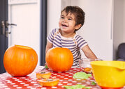 Boy carving pumpkin in kitchen - CUF51086