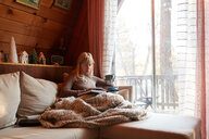 Woman reading book on sofa at home - ISF21329