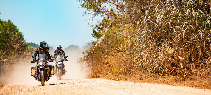 Male friends riding ADV motorcycles on dusty dirt road in Cambodia - ISF21383