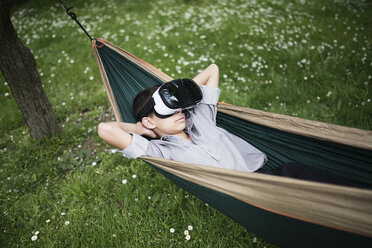 Mixed Race boy laying in hammock wearing virtual reality goggles - BLEF03106