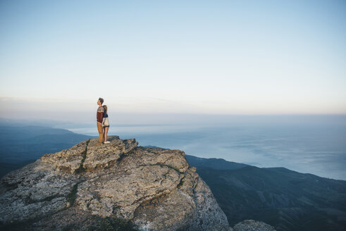 Caucasian couple standing back to back on mountain - BLEF03127