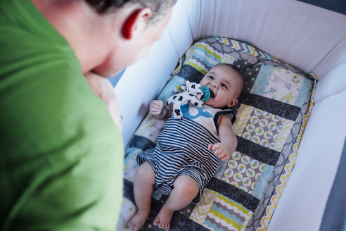 Father watching baby son in crib - BLEF03193