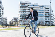 Man cycling past multi-storey building, Milan, Lombardia, Italy - CUF51147