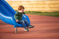 Boy playing on slide in playground - CUF51186