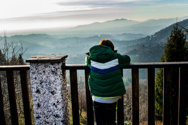 Boy looking out at mountain valley landscape from balcony, rear view, Piani Resinelli, Lombardy, Italy - CUF51189