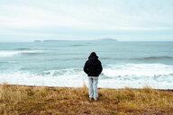 Tourist enjoying ocean view, Eskifjörður, Sudur-Mulasysla, Iceland - CUF51255