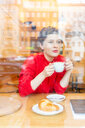 Mid adult woman in cafe drinking coffee looking out, window view - CUF51267