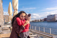 Mother hugging daughter by river, Berlin, Germany - CUF51273
