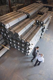 Businessmen talking near steel tubing in warehouse - JUIF00913