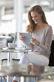 Smiling woman reading digital tablet at cafe table - JUIF00916