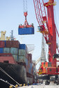 Cranes unloading container ship at commercial dock - JUIF00922