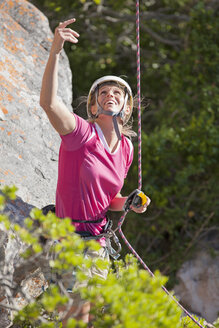 Smiling female rock climber looking up and gesturing - JUIF00934
