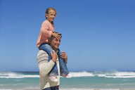 Father carrying daughter on shoulders on sunny beach - JUIF00958