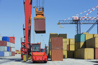 Crane lifting cargo container at commercial dock - JUIF01000