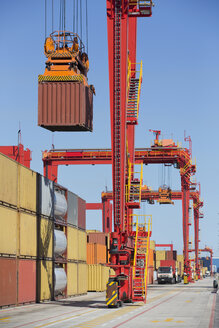 Crane lifting cargo container at commercial dock - JUIF01003