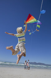 Boy jumping and reaching for kite on sunny beach - JUIF01018