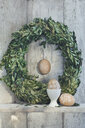 Painted Easter eggs, egg cup and box tree wreath on shelf in front of wooden wall - ASF06399