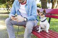 Portrait of dog sitting besides his owner on park bench - WPEF01506