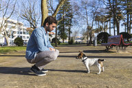 Young man teaching his dog in a park - WPEF01512