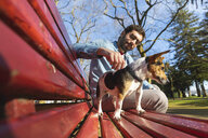 Young man sitting on park bench stroking his dog - WPEF01515