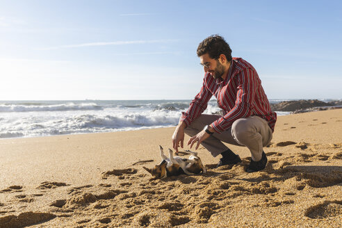 Portugal, Porto, young man playing on the beach with his dog - WPEF01521